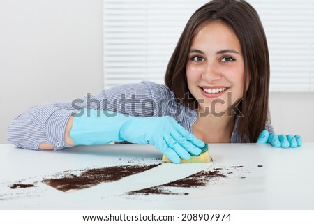 Close-up of woman's hand cleaning dirt on table with sponge at home - stock photo