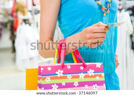 Close-up of woman?s hand giving plastic card in the mall - stock photo