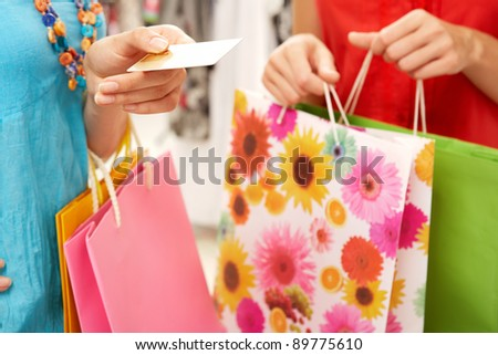 Close-up of woman?s hand holding credit card with another female near by during shopping - stock photo