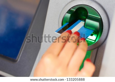 Close-up of woman's hand inserting debit card into an ATM machine. Horizontal shot. - stock photo