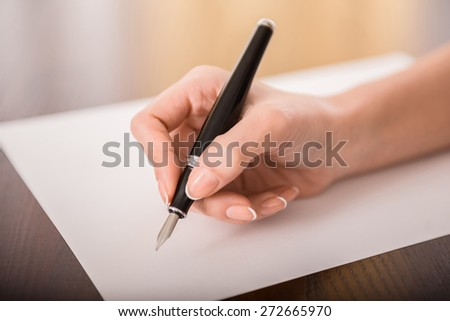 Close-up of woman's hand is writing on paper. - stock photo