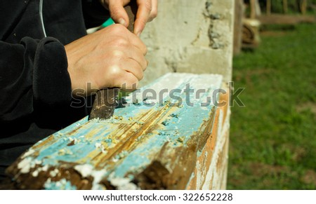 Close-up of woman's hand peeling a white paint from a piece of Wood - stock photo