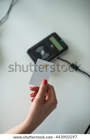Close up of woman's hand putting a credit card on a machine.