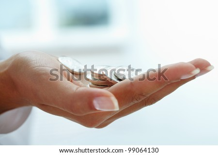 Close-up of woman�¢??s hand with heap of coins - stock photo