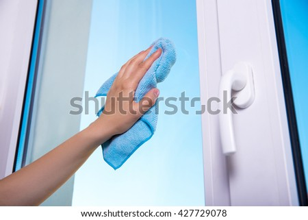 close up of woman's hand with special rag cleaning window - stock photo