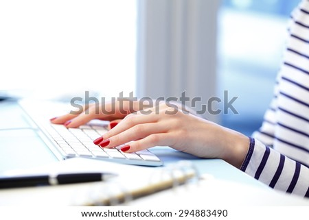 Close-up of woman's hands are typing on a computer keyboard. Young businesswoman sitting at office and working online. - stock photo