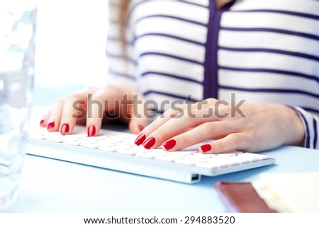 Close-up of woman's hands are typing on a computer keyboard. Young businesswoman sitting at office and working on presentation.  - stock photo