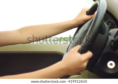 Close up of woman's hands driving a car. Picture of girl's arms holding steering wheel inside auto. Young female sitting indoor on summer outdoor background. no face - stock photo
