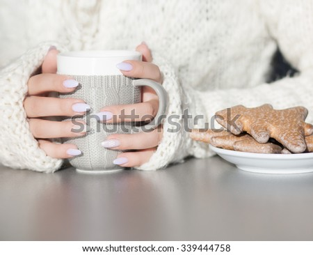 Close up of woman's hands holding cup of hot coffee drink. She is wearing warm cardigan. Christmas gingerbread on the table. Winter chill out and lifestyle concept. - stock photo