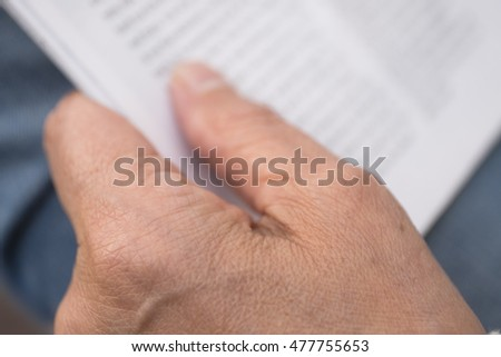 Close-up of woman's hands while reading a magazine, swallow depth of field