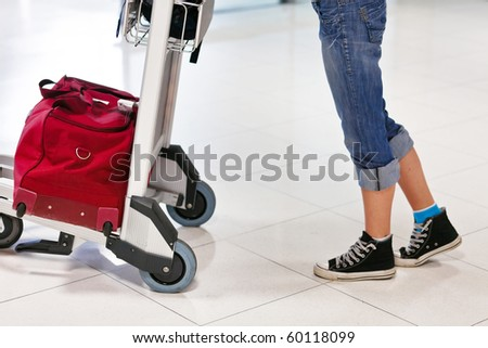 Close up of woman's legs and feet with luggage cart with bag - stock photo