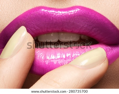Close-up of woman's lips with fashion hot pink lipstick makeup. Beauty macro sexy make-up with naturel beige manicure.  - stock photo
