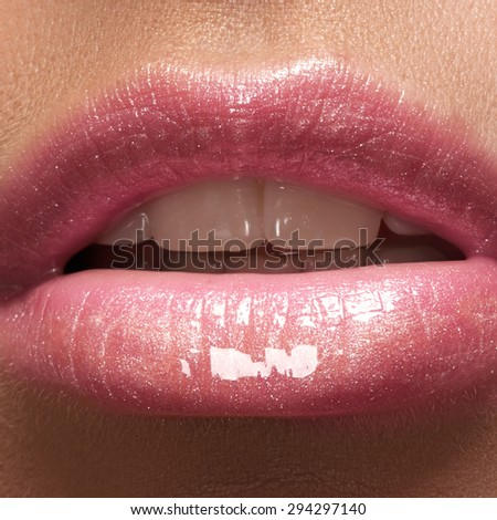 Close-up of woman's lips with fashion natural rose lipstick makeup. Horizontal macro sexy pale lipgloss make-up  - stock photo