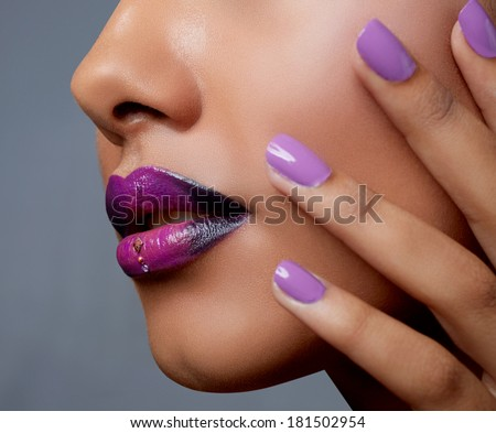 Close-up of woman's mouth with dark fashion purple lipstick with ombre effect. Hand with purple nailpolish touching tanned face