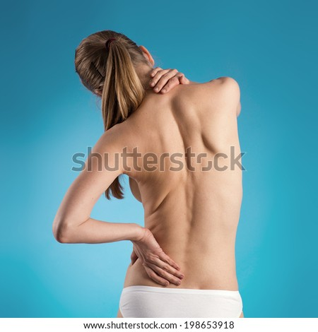Close-up of woman's naked back over blue background. Health and body care concept.