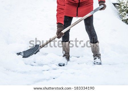 Close-up of Woman Shoveling her Parking lot after Snowstorm - stock photo
