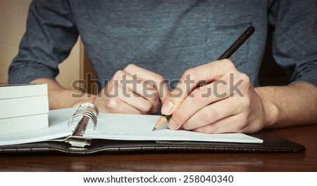 close-up of woman sitting at desk and writing reminder on agenda. natural light - stock photo