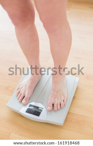 Close up of woman standing on weighing scale in a fitness studio - stock photo