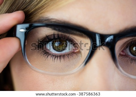 Close-up of woman touching her glasses with two fingers