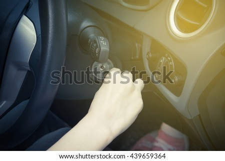 Close up of woman turning on his car with sunrise - stock photo