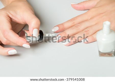 Close Up of Woman Using Applicator Brush to Apply White Polish to Nails with Bottle Close By on White Surface with Copy Space - stock photo