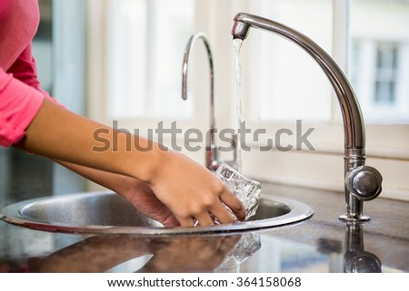 Close up of woman washing glass in the kitchen