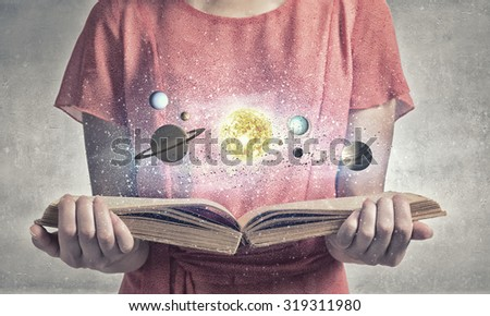 Close up of woman with book exploring planets of sun system - stock photo