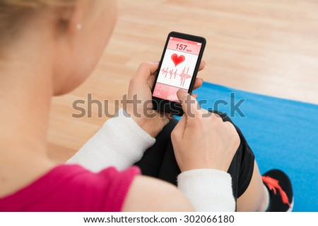 Close-up Of Woman With Mobile Phone Showing Pulse Rate - stock photo