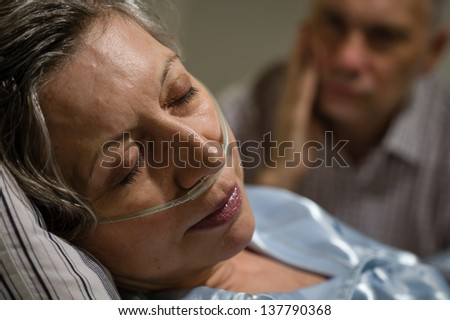 Close up of woman with nasal cannula and worried husband - stock photo