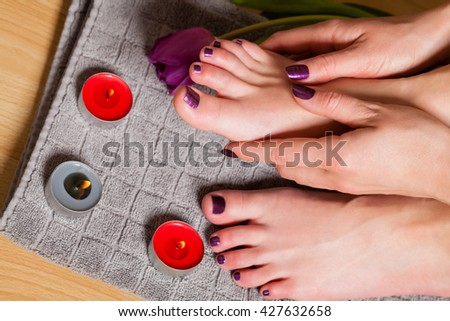 Close up of woman with pedicure and manicure done in a lovely deep purple beside lit candles and fresh tulip - stock photo