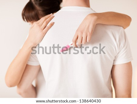 close up of woman with pregnancy test hugging man - stock photo