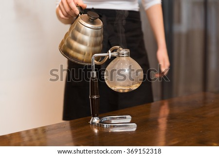 close up of woman with siphon coffee maker and pot