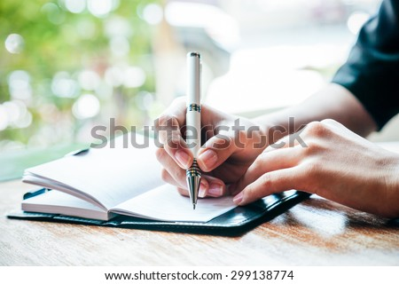 close up of woman writing her journal  - stock photo