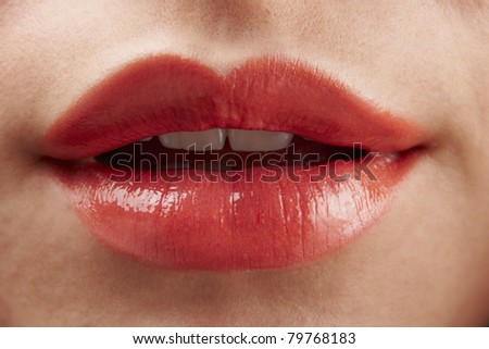 Close-up of womans lips with red glossy lipstick