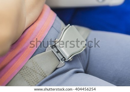 Close-up of women fastening security belt in airplane.selective focus. - stock photo