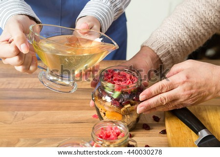 Close up of women preparing sweet preserves and pouring honey on dried fruit mix. In the jar there are walnuts, cranberries, figs, melon and papaya. - stock photo