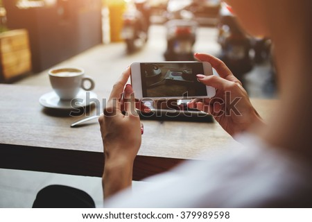 Close up of women's hands photographing sweet dessert on mobile phone for social network picture, hipster girl making photo with cell telephone camera of her morning breakfast while sitting in cafe - stock photo