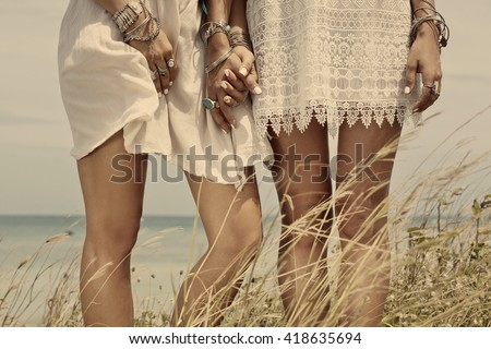 close up of women`s legs in boho style white dresses