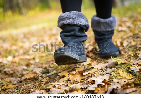 Close up of women's shoe treads on autumn forest footpath