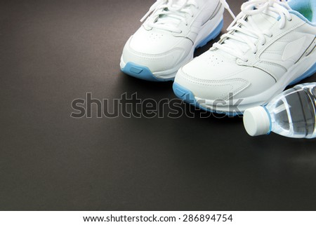 Close up of women's sport shoes and mineral water on black background - stock photo