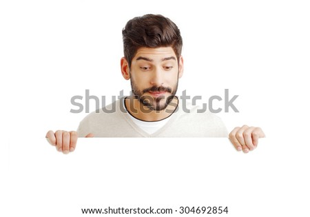 Close-up of wondering businessman holding a blank signboard while standing against white background.  - stock photo
