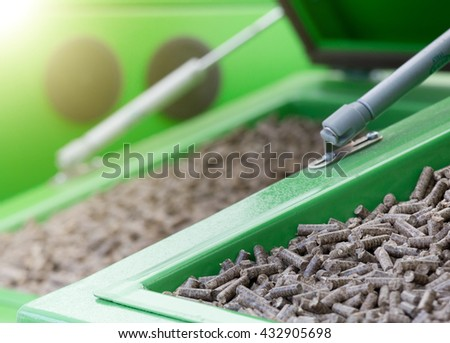 Close up of wood pellets in green container - stock photo