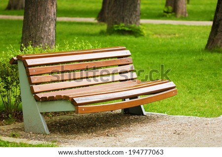 Close-up of wooden bench in park. Peaceful place with green grass.
