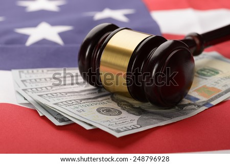 Close-up Of Wooden Brown Gavel On Usa Dollar Banknotes And American Flag - stock photo