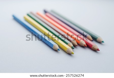 Close up of wooden colored crayons over blue background, shallow depth of field composition - stock photo