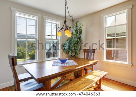 Close-up of wooden dining table with two chairs and bench. House interior. Northwest, USA