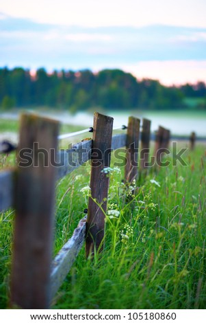 Close up of wooden fence on field on foggy morning - stock photo