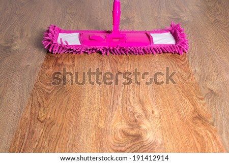 close up of wooden floor with pink cleaning mop - before after - stock photo