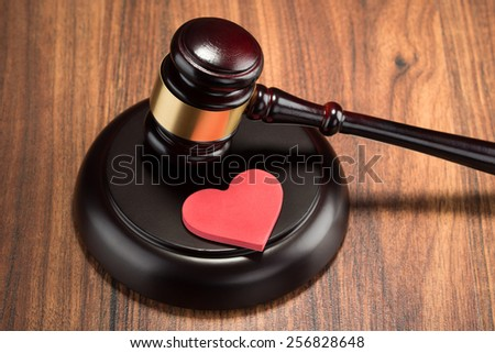 Close-up Of Wooden Gavel And Red Heart On Table - stock photo