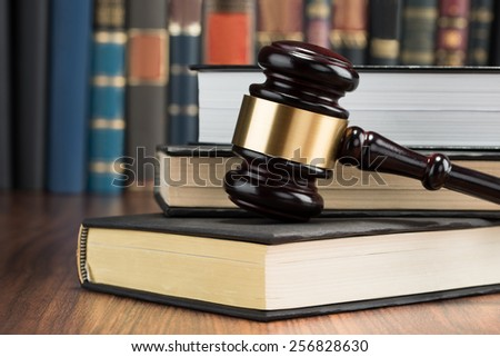Close-up Of Wooden Gavel With Stack Of Books On Table - stock photo